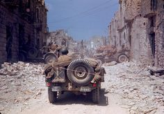 American jeeps travel through a bombed-out town