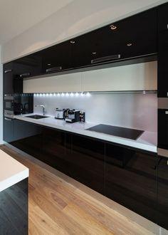 black kitchen design ideas white countertop backsplash wood flooring under cabinet lighting