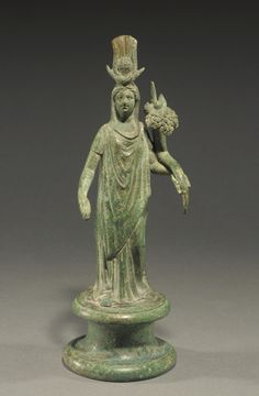 ROMAN-EGYPTIAN BRONZE ISIS-FORTUNA  Wearing elaborate sun-disk-crescent-horn-plume headdress, holding cornucopia, fragment of rudder.  Ca. 2nd Century AD  H. 8 in. (20.3 cm)  Ex R.K. collection, Tecumseh, Michigan, acquired from Royal-Athena in June 1989.  Published: J. Eisenberg, The Age of Cleopatra (1988), no. 78.  On loan to Picker Art Gallery, Colgate Univ.; Fitchburg Art Museum - 1990-2016.