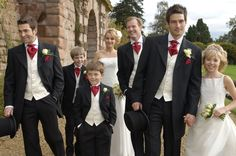 White vest, red tie, black suit?  But groomsmen with black waistcoat so groom stands out!