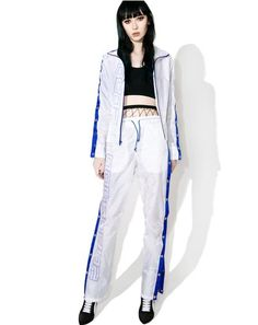 """Brashy 2000 Tracksuit Pants won't be experiencing no digital meltdown, bb. These tracksuit pants are glitch free featuring a semi-transparent ripstop nylon construction, blue stripes and snap button detail on the sides, drawstring waistband, and """"2000"""" printed on the front."""