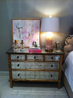 Bijou and Boheme Reader's Home - Beautiful bedroom with Etsy Wink of Pink Art on gold mirrored chest nightstand filled with rose quart lamp and Chanel books.