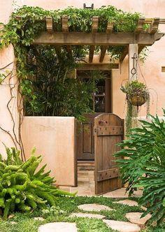 Un techo de maderas con vegetación colgante y puerta rústica dan a ...