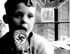 """This young boy is eating what's called a """"Nazi Pop"""". These were created in Germany to influence Nazi beliefs, and implement Hitler into the lives of young children. The """"pops"""" helped HItler gain followers in his time of power."""