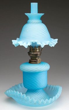 """EXTREMELY RARE SWIRL OPALESCENT THREE-PART MINIATURE LAMP, beautiful blue glass with satin finish, drop-in font sits in a ruffled upturned tri-form saucer-type base, matching bell shaped shade with a flared top and ruffled bottom rim, blue opalescent panel-optic glass chimney. Period burner with thumbwheel marked """"F. S. & C. L'D"""" and shade holder. Attributed to Stevens & Williams."""