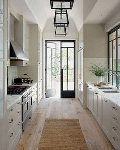 Perfect balance of light in this fresh crisp kitchen. The limed oak floor is oh so airy and the walls and ceiling are puncuated by the black metal frame doors, windows and iron lanterns.