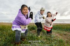 Photo of Yupik Eskimo women and man, wearing traditional dress, dancing outdoors on Bering Sea shore in grass,  Summer Nome, Alaska
