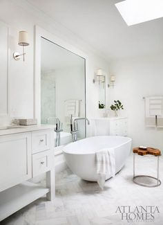 Classic bathroom with freestanding tub, marble chevron tile, Visual Comfort lighting.
