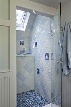 antiqued Delft tiles, shower ceiling follows roofline, skylight added; nice color and tile variety; antiqued ladder can be used as towel rack behind a claw-foot bathtub