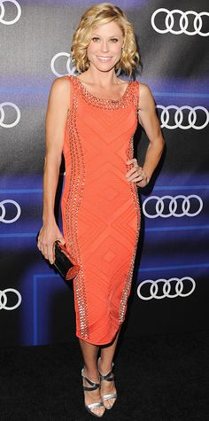 Modern Family star Julie Bowen lit up the red carpet at the Audi Emmy Week Celebration in a vibrant orange curve-hugging Herve Leger dress with silver grommets along the sides and neckline, carrying the metallic accent over to her mirrored clutch and silver Giuseppe Zanotti sandals. #InStyle