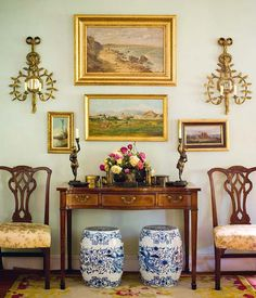 Entry vignette with gilt sconces, oil paintings, garden stools and chairs - Rosa Bernal