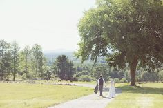 Lovely shot of the bride and groom walking outside of the Fruitlands Museum in Harvard, MA.  This wedding venue has the most amazing view of the mountains, and a stunning white wedding tent for an outdoor reception!