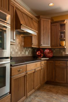 Country style kitchen with stainless steel appliances, tile backsplash, and tile floor.