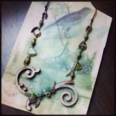 Handgemaakte  ketting van glaskralen knopen, metalen veertjes en lederen flourish vorm. Aan weerskanten draagbaar.