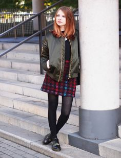 The Fashionable Blog. Black sweater+colourfull houndstooth printed skirt+black tights+black laced shoes with camo print+khaki bomber jacket+necklace+black bucket bag. Fall Casual Outfit 2016