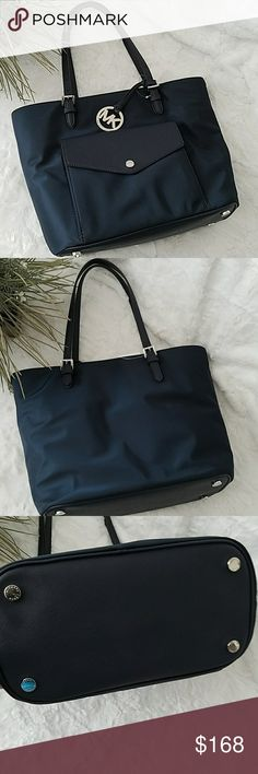"""☡OFFER NOW☡ Michael Kors Large Tote Beautiful navy nylon fabric with silver tone hardware Michael Kors Jet Set tote. Monogram print lined interiors with a center zippered wall pocket. Inner zippered pocket and four open slip pockets; front flap pocket with 6 card slots. Dual leather straps with a drop of about 8""""; Protective feet on bottom. 12"""" (L) at the bottom tapering to 15"""" (L) at the top x 11"""" (H) x 6"""" (W). 100% authentic. No damages. Pictures are taken to the best of my abilities so…"""