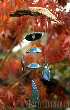 How to make a clay and wood wind chime DIY -  Organic clay shapes strung up on branches make for beautiful art that brings melody and movement to the garden.
