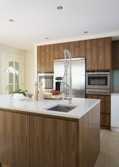 wood grain dominate cabinets, white counters, white walls and ceiling, stone floor a tone between wood stain and wall color, stainless appliances