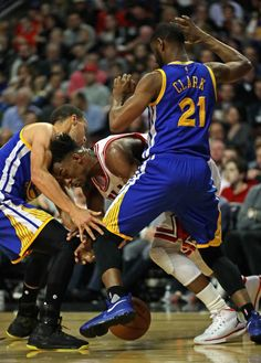 Jimmy Butler of the Chicago Bulls is pressured by Stephen Curry and Ian Clark of the Golden State Warriors at the United Center on March 2 2017 in...