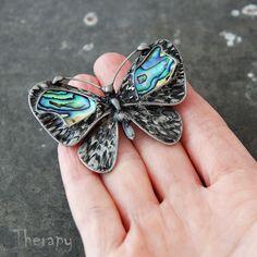 Papilio paualis Cínem pájená brož s paua mušlemi. Velikost brože je 5,7 x 4 cm. Brož je vhodná na silnější tkaniny (kabáty, saka). Brožový můstek s pojistkou. Vše kromě brožového můstku je ruční práce. Patinováno, leštěno, ošetřeno antioxidantem.