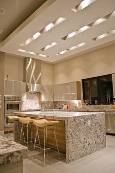 This kitchen is amazing! Love the island, stools, and unique ceiling lighting.