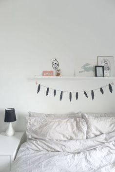 prateleira acima da cama com pequenos quadros e objetos decorativos, bandeirinha em formato de penas na parede