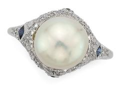 Platinum, Natural Pearl, Diamond and Sapphire Ring   Platinum, centering one pearl* approximately 9.3 mm., the pierced mount accented by 4 diamond-shaped cabochon sapphires, set with numerous small old European-cut diamonds, circa 1915