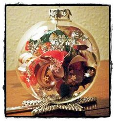Yule Ball Ornament - Use festive paper scraps, ribbon and confetti to create this easy Christmas ball ornament. The various Christmas materials show through the clear glass ornament. #tutorial