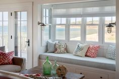 This light, serene living room is inspired by the ocean showcased through its many windows. The window seat cushion draws from hue of the ocean, and coastal accessories complete the beachy look.