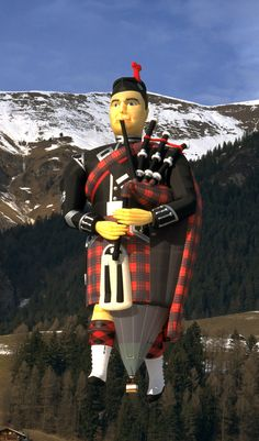 "Cameron Balloons built Special Shape Balloon - Pipe Major ""wearing"" red Fraser tartan and a sgian-dubh (skee-en-doo) Scottish Gaelic pronunciation for the small, single-edged knife worn as part of traditional Scottish Highland dress along with the kilt (which traditionally uses 8yards of fabric) the sporran (instead of pockets) and the plaid (part of the formal highland dress & useful blanket-shawl for keeping out the typical dreigh (dreary) winter weather!)."