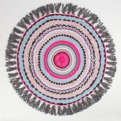 Tämä matto (halkaisija 76 cm ilman tupsuja) on punottu erivärisistä akryylilangoista pyöreällä punontakehyksellä.