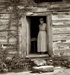 """Caroline Atwater standing in the kitchen door of her log house."" Orange County, North Carolina, July 1939"