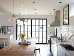 Three pendant lights from West Elm are suspended over a knotty-surfaced farm table in the kitchen, one of the few holdovers from the homeowners' previous decor.