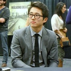Stephen Yeun looking anything but interested. Is the lady behind him the one who stabbed herself in Season 4, Episode 1?