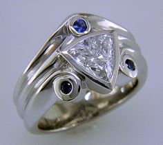 A trilliant diamond ring with three small sapphires.