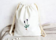 LAVENDER HAND EMBROIDERED DRAWSTRING BAG  Delicate hand embroidery pouch with a beautiful lavender botanical embroidery for all lavender lovers. It is a beautiful pouch made from white thick linen with a rustic look. You can use it as a make up bag, holiday travel bag, home decor bag, you can also use this bag to store vegetables, drie nuts. Store Vegetables, Embroidered Bag, Natural Linen, Holiday Travel, Bag Storage, Travel Bag, Hand Embroidery, Lavender, Delicate