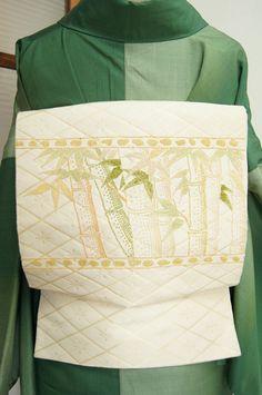 金の業平菱模様が大胆に浮かび上がる白の地に、若草緑、柳色、たまご色、練色、象牙色などの柔らかな色糸も心地よく、相良刺繍と思われる立体的なステッチで刺繍された竹の模様が美しい、つくり帯です。