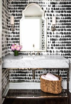 Glam powder room with printed black and white wallpaper, a silver mirror, and flowers