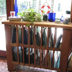 A shelving unit up against a window really gives a lot of extra light to see your glass. If there is no window available perhaps a light behind the shelves would help.