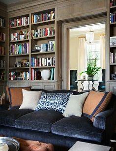 Deep blue linen velvet sofa with throw pillows.