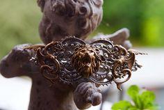 Barrette à cheveux (8cm de largeur) composée de plusieurs estampes en métal vieilli. Deux vouivres se font face (dorées) et enserrent une tête de lion rugissant (dorée aussi). L'estampe principale...