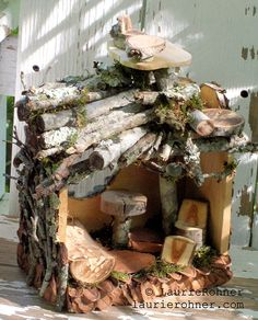 Woodland fairy houses, magical, mystical, one of a kind, custom sculpted, woodland cottages moss covered naturally decorated furnished with handmade one of a kind fairy chairs tables beds are nature art garden sculpture by Laurie Rohner.