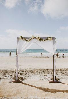 Chic arbor on the beach, cream florals, white fabric // Lauren Scotti Photography