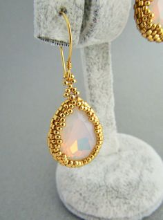 24k gold plated Sterling Silver Teardrop Dangle Earrings.  Crystal Opal White Teardrop Crystal Stones surrounded by galvanized gold delica seed beads .  Finished with gold vermeil coil ear wires which are sterling silver plated with 24 carat gold.  Earrings lenght is 4 cm (1.57 inch).  Crystal stones size is 18x13 mm.  Earrings come packed in a gift box.  Thank you for watching.