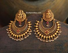 22 carat gold antique toned latest model chandbalis with Goddess Lakshmi tops from Navrathan Jewellers, Bangalore. The earrings have pearl clusters hanging at the bottom.  Related PostsAntique Lakshmi ChandbalisAntique Jhumkis Necklace with Nakshi pendantNavarathan Jewellers Latest Jewellery CollectionDivine Nakshi Temple Jewellery SetMango Haram with Ganesh MotifsAntique Gold Mesh Necklace