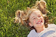 A little girl lying in the soft summer grass, her face alight with laughter.