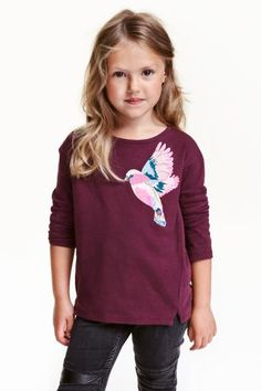 Jersey top with sequins: Long-sleeved top in cotton jersey with sequined embroidery and short slits at the front. Slightly longer at the back.