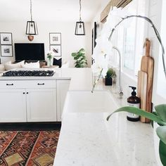 From the iron pendant lanterns on the ceiling to the vintage Turkish rug on the floor, we can't get enough of this chic, modern kitchen's style!