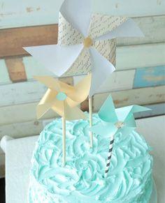 Topo de bolo de catavento em cores neutras num bolo turquesa (azul tiffany). Foto: Wayfair.