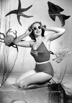 Swim Suit gaily embroidered fishes add a touch of colour to the all over stocking stitch pattern.May 1949, General, Swim Wear1949 (c)TopFoto / Alinari Archives